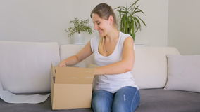 Portrait of cheerful young woman opening parcel box with dress stock video footage