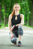 Portrait of cheerful young woman ready to start running session. Stock Images
