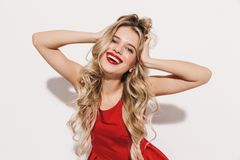 Portrait of a cheerful young woman in red dress standing stock photo