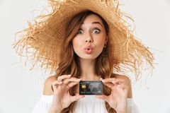 Portrait of cheerful young woman 20s wearing big straw hat rejoicing while holding credit card, isolated over white background. Portrait of cheerful young woman stock photo
