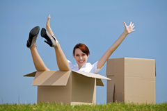 Portrait of cheerful young woman sitting in cardboard box at park with arms outstretched Stock Image