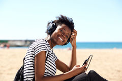 Young woman sitting outdoors with mobile phone and listening to music on headphones Royalty Free Stock Image