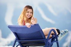 Sexy female skier on blue deck chair near skis at ski resort Stock Photos