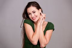 Cheerful young woman smiling with hands clasp together. Portrait of cheerful young woman smiling with hands clasp together Stock Photos