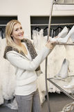 Portrait of a cheerful young woman standing by footwear standing in bridal store Stock Photos