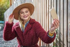 Happy blond girl making selfie on smartphone outside stock photo