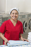 Portrait of a cheerful young woman with towel in Laundromat Stock Image
