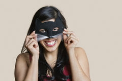 Portrait of a cheerful young woman wearing eye mask over colored background Royalty Free Stock Photography