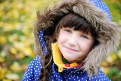Portrait of cheerfull child girl in blue coat. Outdoor portrait of cheerfull little girl in blue coat with a hood Royalty Free Stock Images