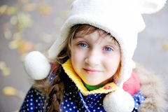 Portrait of cheerfull child girl in white hat. Outdoor portrait of cheerfull little girl in blue coat and white hat Royalty Free Stock Photos