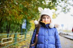 Portrait of cheerfull child girl in white hat. Outdoor portrait of cheerfull little girl in blue coat and white hat Stock Photo