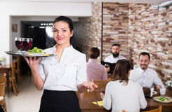 Portrait of cheerfull female waiter carrying order. For visitors in country restaurant Stock Image