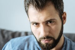 Portrait of a cheerless handsome man looking at you. Sad eyes. Portrait of a cheerless gloomy handsome man looking at you while feeling unhappy Royalty Free Stock Photography