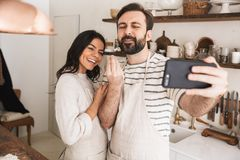 Portrait of cheery couple man and woman 30s wearing aprons taking selfie photo while cooking at home. Portrait of cheery couple men and women 30s wearing aprons stock photo