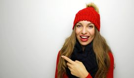 Portrait of a cheery woman dressed in red sweater and blue scarf. Pointing finger away isolated over white background. Copy space stock image