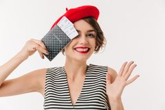 Portrait of a cheery woman wearing red beret. Holding passport at her face isolated over white background Royalty Free Stock Image