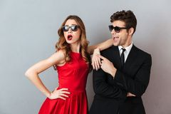 Portrait of a cheery young couple dressed in formal wear. And sunglasses posing while standing over gray wall background Royalty Free Stock Photo