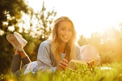 Portrait of a cheery young girl with backpack. Laying on a grass at the park, reading a book Royalty Free Stock Image
