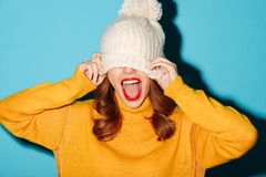 Portrait of a cheery young girl dressed in winter hat. Laughing  over blue background Royalty Free Stock Photography