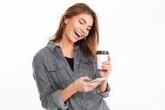 Portrait of a cheery young girl using mobile phone. While holding coffee cup isolated over white background Royalty Free Stock Photo