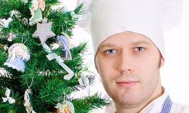 Portrait of chef cook near xmas tree. Royalty Free Stock Image