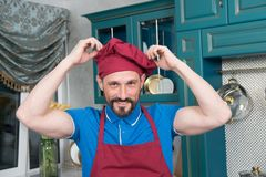 Portrait of chef in hat and apron at kitchen. Man in kitchen uniform. stock photo