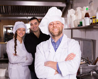 Portrait of chef with helpers Stock Images