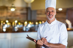 Portrait of chef holding a clipboard. Portrait of chef standing in restaurant holding a clipboard stock photography