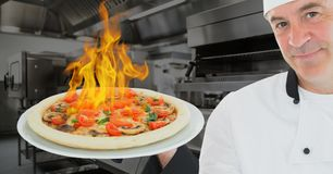 Portrait of chef holding pizza with burning fire. In kitchen Stock Image