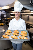 Portrait of a chef holding tray of croissants Stock Photography