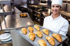 Portrait of a chef holding tray of croissants Royalty Free Stock Photos