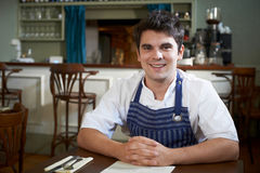 Portrait Of Chef Sitting At Table In Restaurant Royalty Free Stock Image