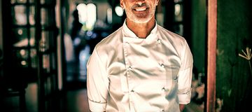 Portrait of chef standing with hands behind back. In restaurant royalty free stock image