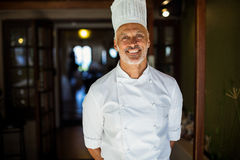 Portrait of chef standing with hands behind back. In restaurant stock image