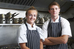 Portrait Of Chef And Trainee In Kitchen. Portrait Of Chef And Trainee Working In Kitchen Stock Photos