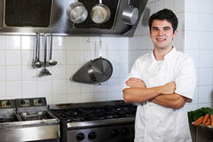 Portrait Of Chef Wearing Whites Standing By Cooker In Kitchen Stock Photos