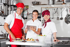 Happy Chefs Using Tablet Computer In Kitchen royalty free stock photos