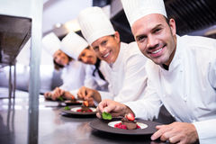 Portrait of chefs team finishing dessert plates Royalty Free Stock Photo