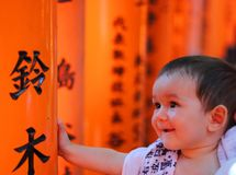 Portrait of a cherful little baby with red colorful toriis of Fushimi Inari Taisha shrine on background. Royalty Free Stock Images