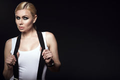 Portrait of chic blond model with pulled back hair and smoky eye make-up wearing white top with suspenders over her shoulders Royalty Free Stock Image