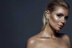 Portrait of chic gorgeous blond woman with wet hair, artistic glittering make-up and the cuff on her ear stock photo