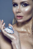 Portrait of chic gorgeous blue-eyed woman with glittering artistic make-up looking straight and holding a shining gem in her palm Royalty Free Stock Photography