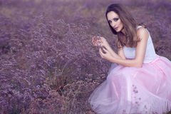 Portrait of chic woman with provocative make up and long hair sitting in the field of violet flowers. royalty free stock photography