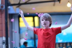 A child with arms raised among the falling petals of flowers. Portrait of a child with arms raised among the falling petals of flowers stock image
