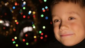 Portrait of a child in the background of Christmas lights stock video