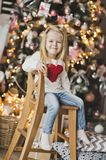Portrait of a child on a background of Christmas tree decorated. The child sits on a wooden chair beside the Christmas tree Royalty Free Stock Photos