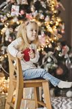 Portrait of a child on a background of Christmas tree decorated. The child sits on a wooden chair beside the Christmas tree Royalty Free Stock Images