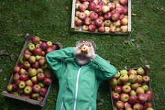 Portrait of Child blond boy lying on the green grass background with pile of apples, holding and eating apple Royalty Free Stock Image