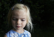 Portrait of child blond girl looking down. In the garden, outside, summertime Royalty Free Stock Photos