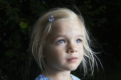 Portrait of child blond girl looking up. In the garden, outside, summertime Stock Images